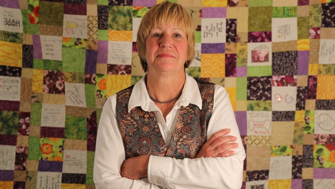 Karen Koehler in front of a get-well quilt put together by friends and family. Koehler, of Park Ridge, underwent experimental treatment for chronic lymphocytic leukemia and is in complete remission.