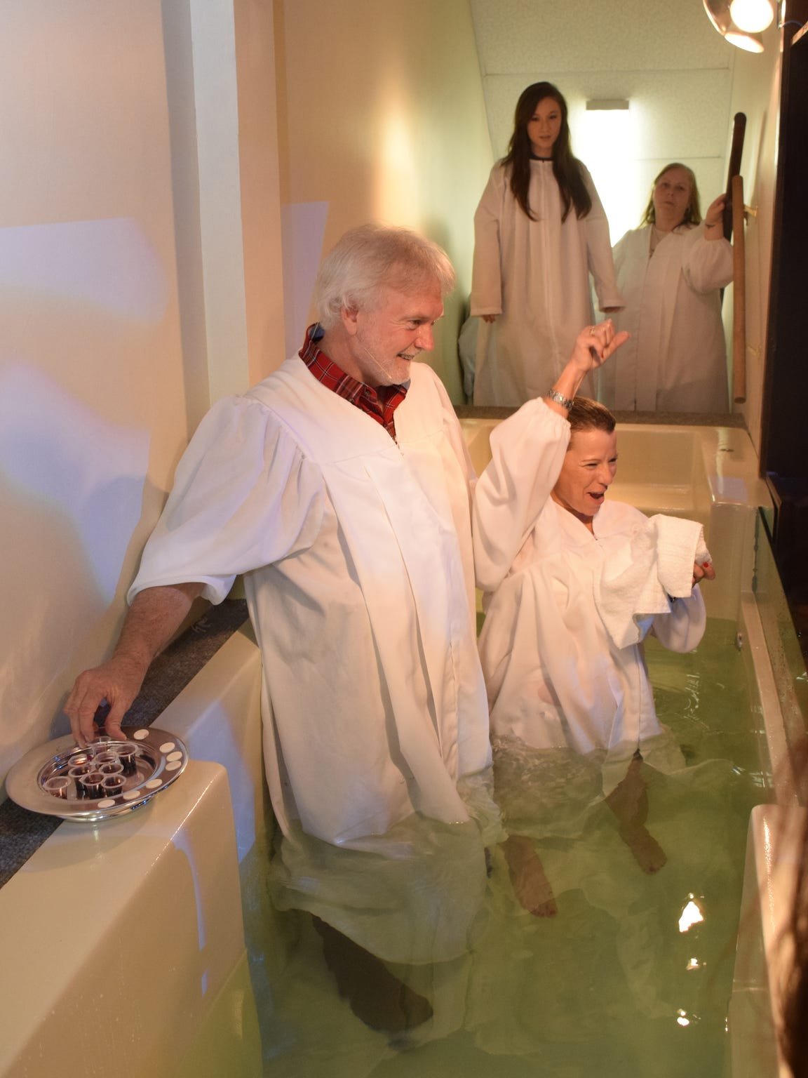Shelia Lowery (right) celebrates after being baptized by Journey Church pastor James Greer (left) Sunday. She was the 100th person baptized at the church this year.