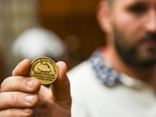 Ryan Ditzler holds a coin DUI Court graduates receive. It reads: 'Lebanon County DUI Court. Today I will do just one thing to help my recovery process.' Nineteen people graduated from Lebanon County's DUI Court program on Tuesday, June 28, 2016.