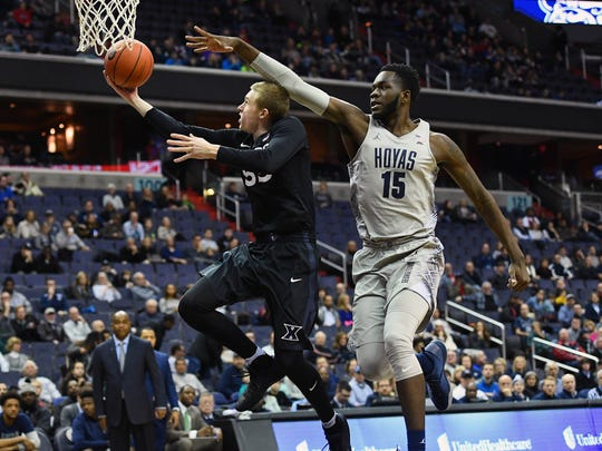Xavier's J.P. Macura shoots as Georgetown's Jessie Govan chases.