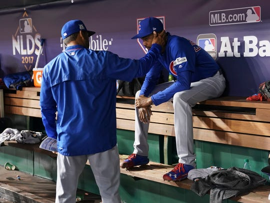 Chicago Cubs bench coach Dave Martinez, left, consoles