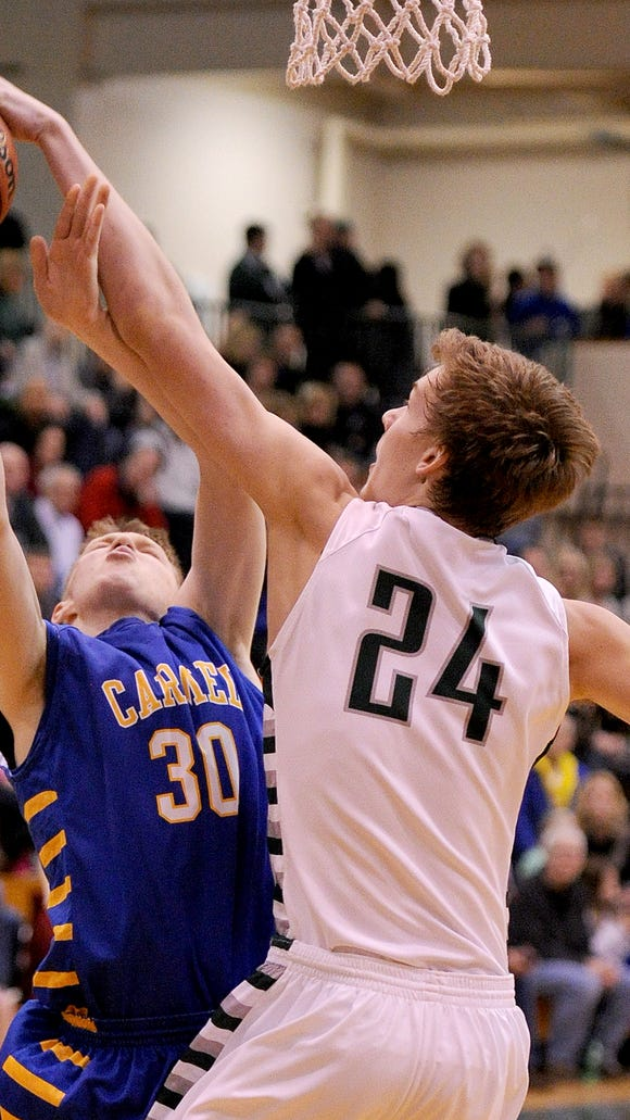 Carmel guard Michael Bruns has his shot blocked by Zionsville center Derrik Smits, Feb. 8, 2014.