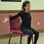 Senior woman doing stretch exercise on chair