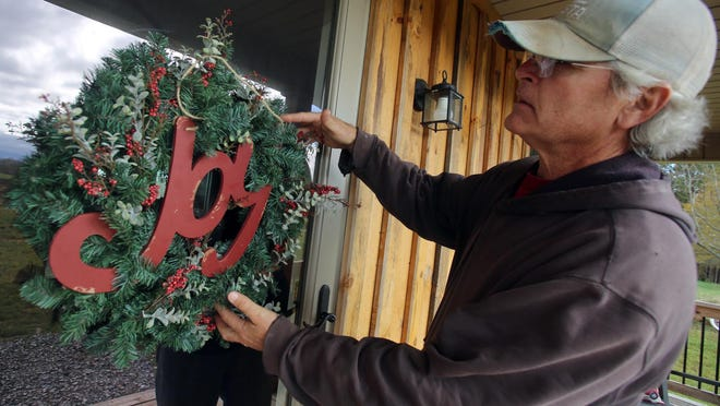 Sandy Swofford adjusts a wreath on the front door at Farmhouse on the Hill on Monday.