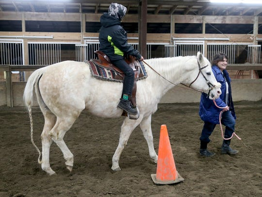 Leah Bethalchmy guides a foster child for a horse ride