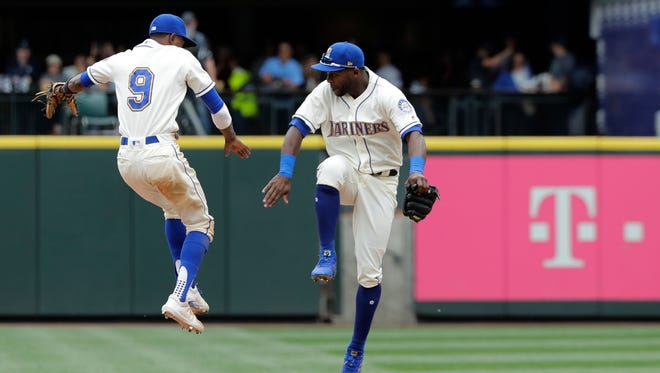 Dee Gordon (9) and Guillermo Heredia of the Mariners celebrate a win over the Kansas City Royals on Sunday.