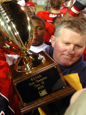 South Panola coach Ricky Woods hold up his fourth consecutive MHSAA Class 5A state championship trophy at Mississippi Veterans Memorial Stadium in Jackson.