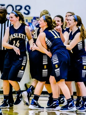 Members of the Haslett girls basketball team celebrate with teammate Annisa Whims ,20, after she sank a bucket to put Haslett up 61-56 in the last seconds of the 3rd overtime of their game with DeWitt Friday February 19, 2016 in DeWitt.  KEVIN W. FOWLER PHOTO