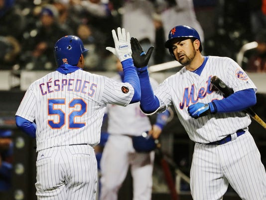 New York Mets' Adrian Gonzalez, right, celebrates with teammate Yoenis Cespedes (52) after Cespedes scored on a single by Todd Frazier during the sixth inning of a baseball game against the Philadelphia Phillies Tuesday, April 3, 2018, in New York. (AP Photo/Frank Franklin II)