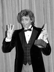 Barry Manilow holds his award for favorite male pop