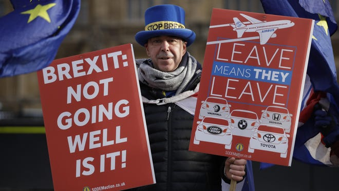 An anti-brexit supporter holds banners in London, Jan. 29, 2019. With Britain's House of Commons bitterly divided on the way forward for Britain's departure from the European Union, lawmakers representing various factions are vying to have their say in the Brexit process after they overwhelmingly rejected the government's divorce agreement two weeks ago.