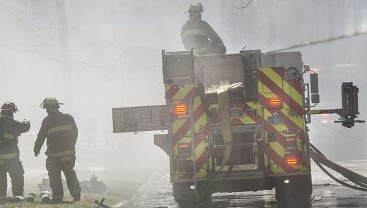 Firefighters pour water on the burning home Wednesday, but their efforts are hampered by high winds and arcing power lines.