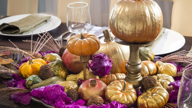 Create a centerpiece for your Thanksgiving table with painted pumpkins placed atop candlesticks and surrounded with more seasonal accents.