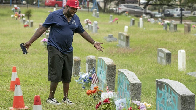 De'Nerick Taylor reacts to seeing his great-grandparents' headstone after it was defaced by vandals at Evergreen Cemetery on Monday.