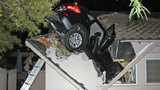 A sport utility vehicle that went airborne early Wednesday and sailed onto the roof of a home in Escondido, Calif., awaits removal.