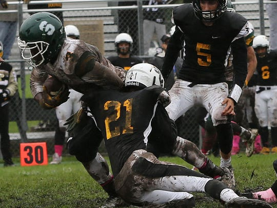 St. Catherine's Luke Letsch hangs on to Martin Luther's Darios Garrett as he struggles for extra yards.