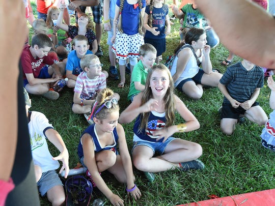 Kids enjoy a magic show at the Red, White & Blue Festival at ASUMH on Saturday.