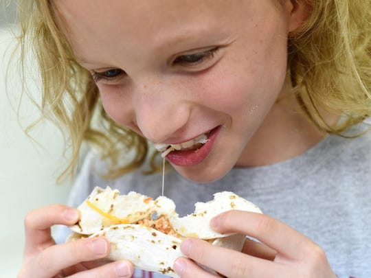 Hendrix Hughes, 10, tastes the Chicken-Cheese Burrito he made.