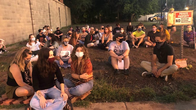 People gather as part of a sit-in Friday at the site of the former Renaissance Community Garden near Main and Sheridan in Peoria.