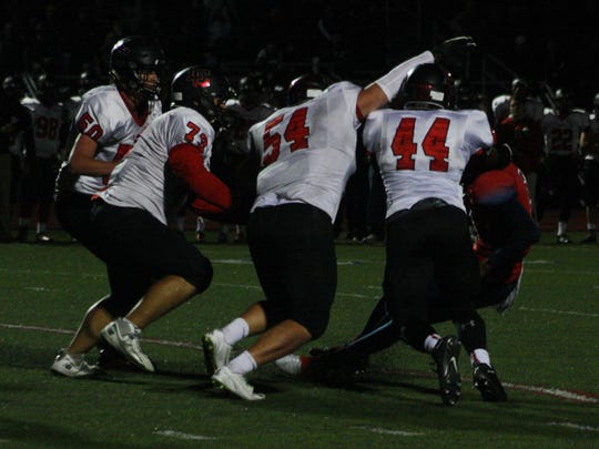 Churchill's defense managed to keep Denzel Adams (red jersey) in check for most of the night, but the senior quarterback made enough plays to win.