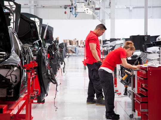 This handout photo made available by Tesla Motors in July 2017 shows workers at the Fremont factory in California.