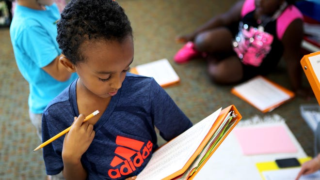 Sammy Habtom practices math with his teacher, Erin Sanders, at Dater Montessori Thursday, September 17, 2015. Dater is one of Cincinnati Public's magnet schools, where the enrollment process was changed this year. The Enquirer/ Meg Vogel