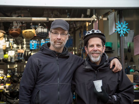 Laurence Clarkberg, of Boxy Bikes, left, and Fernando de Aragon, director of the Ithaca-Tompkins County Transportation Council, stand at a breakfast station Friday in Press Bay Alley.