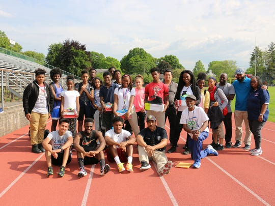 Bernal Harrison, front row wearing a black shirt, with students who have received donations of athletic footwear. Harrison is middle school resource officer in the Plainfield Police Division.