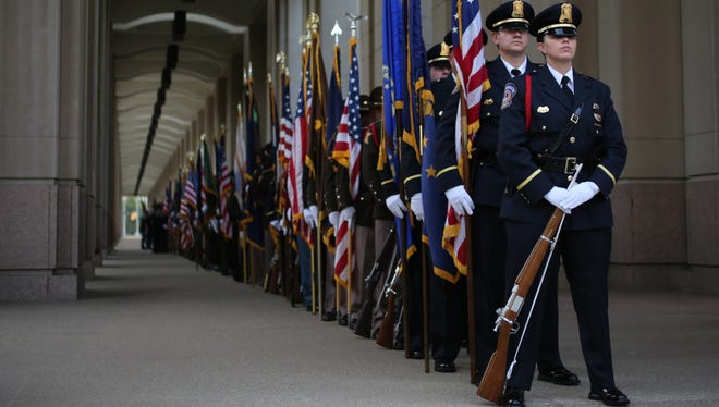 Officer Melissa Moody, with IMPD's North District, heads an interagency honor guard that is part of the Law Enforcement Memorial Service in  Indianapolis on Sept. 9, 2014. The event, on the west side of the Indiana State House, memorialized fallen officers, including Rod Bradway and Perry Renn of IMPD, Jacob Calvin of the Tipton County Sheriff's Office, and Jeffrey Westerfield of the Gary Police Department.