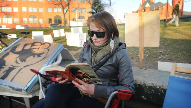 Casey Nocket of Highland reads a book while participating in Occupy Poughkeepsie Monday, December 5, 2011, in the City of Poughkeepsie.