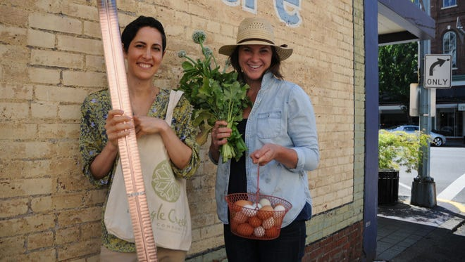 Laura DeVito, left, holding a rooftop solar energy water-heating device, and Jill Snell, holding produce and eggs from the garden of the Pringle Creek Community in South Salem, encourage the public to visit Pringle Creek Community on Saturday during a free tour of several homes, the garden and community spaces.
