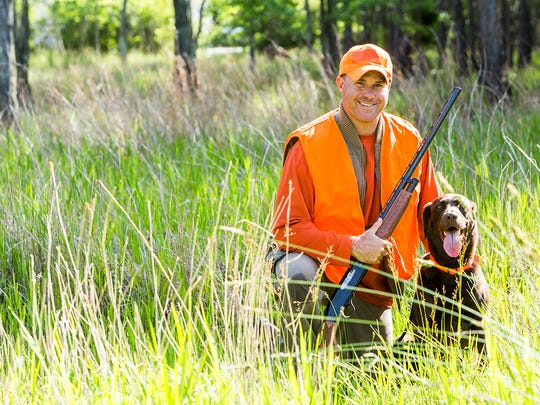 Hunter kneeling on the ground in tall grass, smiling at the camera holding a shotgun.  His hunting dog, a brown labrador retriever, is sitting next to him.  He is wearing an orange safety vest.