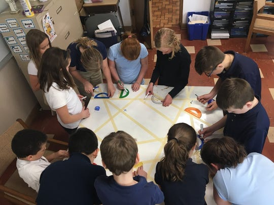 Fourth-grade students at St. Margaret Mary School learned about angles and used protractors to measure angles created in tape designs.