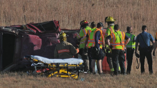 Kansas Highway Patrol, Salina and Saline County emergency responders investigate the red Honda that flipped over several times while traveling on Interstate 70 at 9:20 a.m. Thursday. One person was reported as having serious injuries, one was killed.