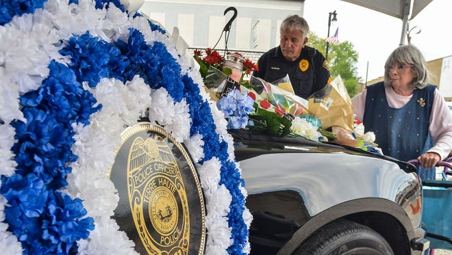 Maridean McCombs leaves a teddy bear and flowers on the patrol car of fallen Terre Haute police officer Rob Pitts, parked outside of THPD headquarters in Terre Haute, Ind., on May 6, 2018. She was assisted by Sgt. Harold Seifers.