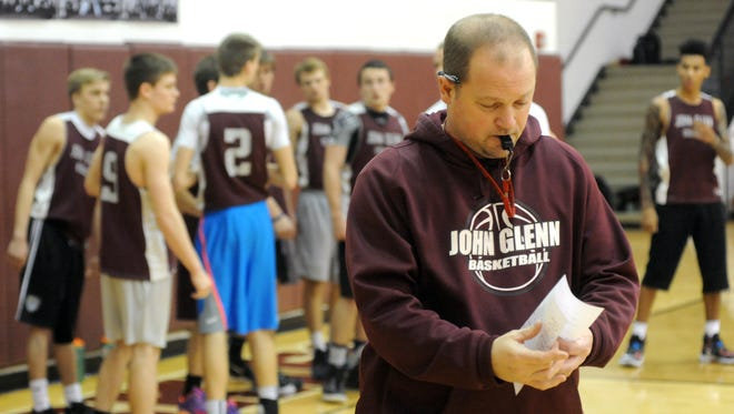 Head Coach Greg Woodard looks over notes before the start of the Muskies' practice session at John Glenn High School. The Muskies are preparing for a tournament run after winning a third-straight MVL title, finishing the regular season 16-0 in the league and 21-1 overall.