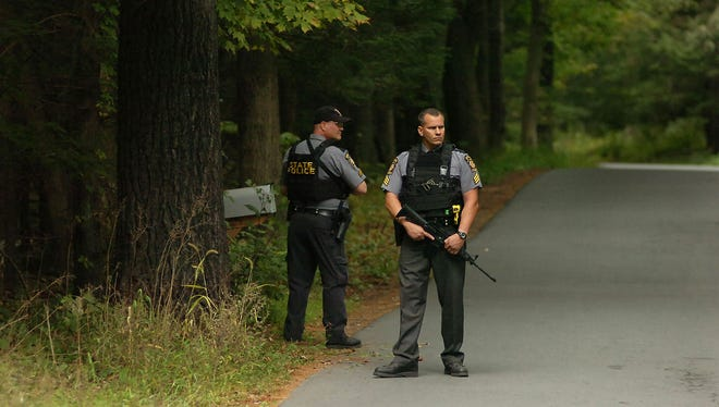 Pennsylvania State Troopers walk along a wooded area near Canadensis, Pa., during a search for suspected killer Eric Frein. Frein is suspected of fatally shooting a state trooper and wounding another.