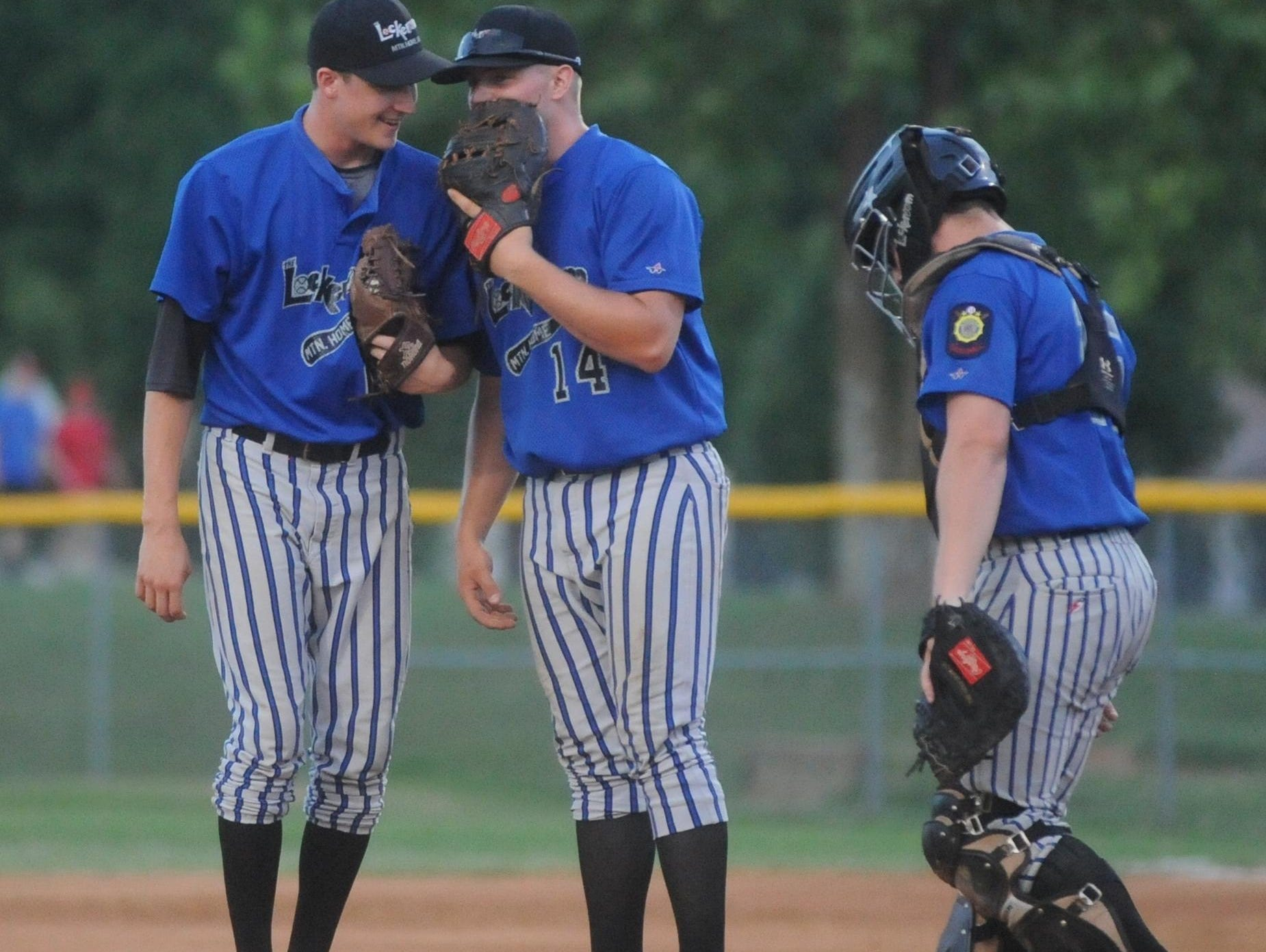 From left, Lockeroom players Ryan Czanstkowski, Cole Anderson and Brody Ninemire meet on the mound during a recent Twin Lakes Classic game at Cooper Park.