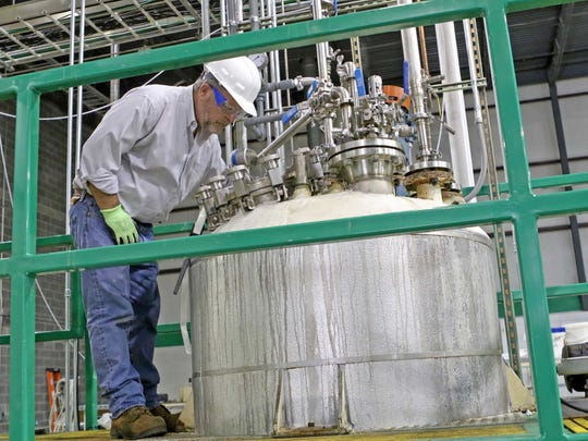 Randy Phillips, director of fermentation technology for White Dog Labs, works on running steam through pipes at the startup's pilot and demonstration facility near New Castle.