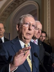 """Senate Majority Leader Mitch McConnell, R-Ky., flanked by Sen. John Thune, R-S.D., left, and Majority Whip John Cornyn, R-Texas, right, talks following a closed-door strategy session at the Capitol in Washington, Tuesday, June 20, 2017. Sen. McConnell says Republicans will have a """"discussion draft"""" of a GOP-only bill scuttling former President Barack Obama's health care law by Thursday."""