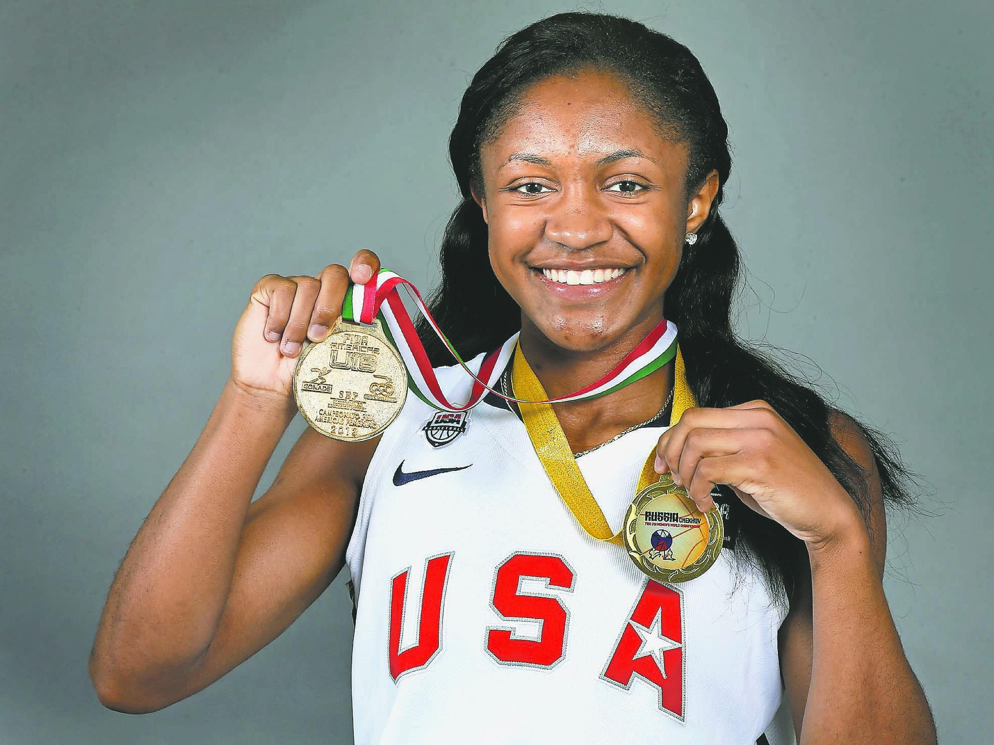 Blackman senior Crystal Dangerfield holds up her two gold medals that she won while competing with the Team USA basketball team.