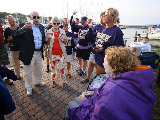 Robert and Margy Hobart, of Binghamton, lead a toast to honor their daughter, Bridgette Hobart Janeczko, as she sits after she successfully swam Seneca Lake nonstop Saturday, Aug. 29. Janeczko exited the waters at the Watkins Glen marina boat launch.