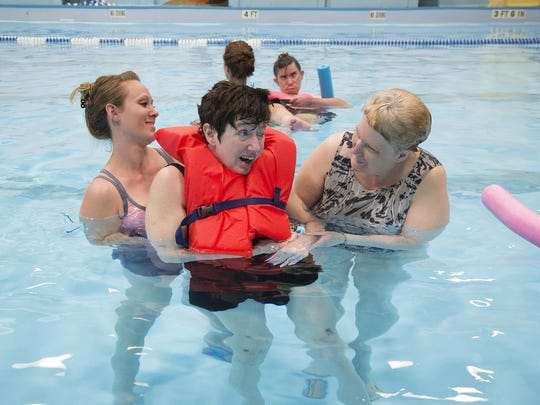 Sarah McMurray, left, and Donna Lunda participate in the BeeHive Homes swim therapy program on May 26 at the Morony Natatorium.