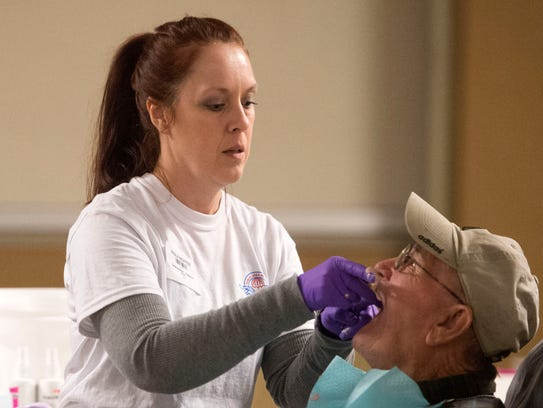 Dental Assistant Paula Nidiffer removes a mold from patient Robert Thompson's mouth at a Remote Area Medical mobile clinic in Chilhowee Park on Feb. 4, 2017. CAITIE MCMEKIN/NEWS SENTINEL