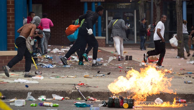 People carrying goods leave a CVS pharmacy Monday in Baltimore.