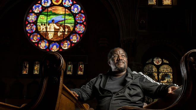 The Rev. Marshall Elijah Hatch at New Mount Pilgrim Missionary Baptist Church on Aug. 6. The stained glass depicts five young victims of recent Chicago violence beneath the four girls killed in the 1963 Birmingham, Alabama, church bombing.