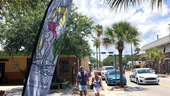 A couple walks by a Save Local NSB banner waving outside of Clancy's Cantina on Flagler Avenue in New Smyrna Beach Tuesday, July 7, 2020. The Save Local NSB project is an alliance of mom and pop shops in New Smyrna Beach to support each other through the coronavirus pandemic.