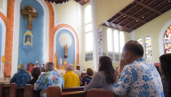 Parishoners attend a Mass in honor of Guam's World