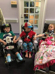 Brothers and sisters Angela, 8, Zachary, 6, and Wyatt, 4, held hands and asked to be near their siblings while they undergo physical therapy.