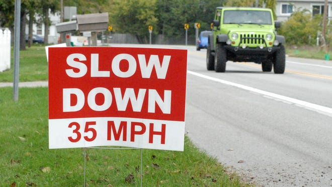 A sign made by Cottrellville Township resident Fred Roberts encourages drivers to slow down near Roberts Landing on M-29.